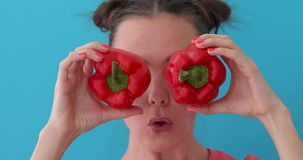 Woman holds pepper in her hands like eyes. Smiling girl covering his eyes with paprika peppers. Happy girl with fresh vegetables. Close up girl fool around at stock footage