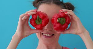 Woman holds pepper in her hands like eyes. Smiling girl covering his eyes with paprika peppers. Happy girl with fresh vegetables. Close up girl fool around at stock video