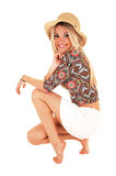 Smiling girl crouching. A beautiful happy blond woman in a white skirt and beige hat crouching Royalty Free Stock Photos