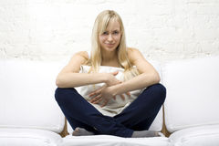 Smiling Girl Cuddling A Pillow On White Couch Stock Image