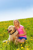 Smiling girl cuddling dog sitting on the grass Royalty Free Stock Image