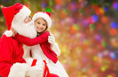 Smiling girl cuddling with santa claus over lights Royalty Free Stock Image