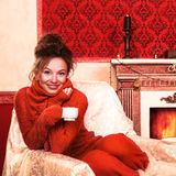 Smiling girl with a cup of coffee in christmas evening in red vi Stock Image