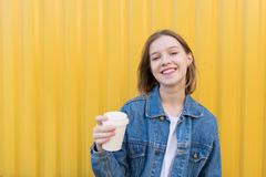 Smiling girl with a cup of coffee in her hands against the background of the yellow wall royalty free stock photography
