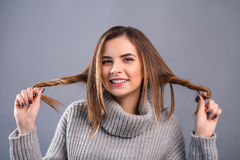 Smiling girl curling her hair Stock Photo