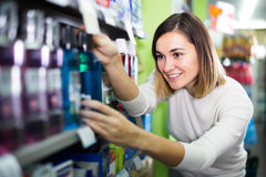 smiling girl customer looking for effective mouthwash in supermarket royalty free stock photos