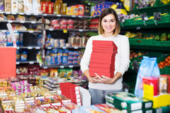 Smiling girl customer looking for tasty sweets in supermarket Royalty Free Stock Photo