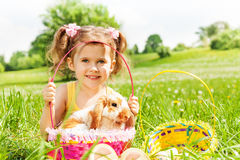 Smiling girl with cute rabbit and baskets in park Royalty Free Stock Images