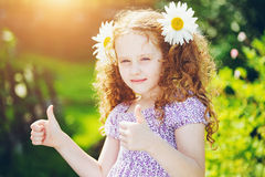 Smiling girl with daisy in her hairs, showing thumbs up. Royalty Free Stock Images