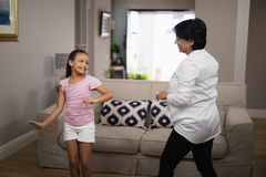 Smiling girl dancing with grandmother. At home royalty free stock photography
