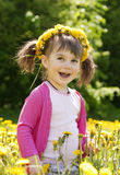 A smiling girl with the dandelion. A smiling girl sitting on the dandelion field with the dandelion garland Stock Photo