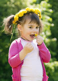 A smiling girl with the dandelion. A smiling girl sitting on the dandelion field with the dandelion garland Stock Image