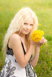 Smiling girl with dandelions. Smiling young girl with dandelions on meadow in spring royalty free stock photography