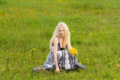 Smiling girl with dandelions on. Smiling young girl with dandelions on meadow, copy space royalty free stock images