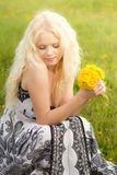 Smiling girl with dandelions,. Smiling young girl with dandelions on meadow in spring, looking down royalty free stock photography