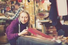 Smiling girl deciding on new belt in leather workshop Stock Image