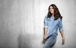 Smiling girl in denim with curly hair. Brunette smiling girl in denim with curly hair on gray cement backround Stock Images