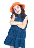 Smiling girl in a denim dress and orange hat Royalty Free Stock Image
