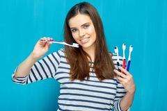 Smiling girl with dental braces holding toothy brush. Blue wall background Stock Images