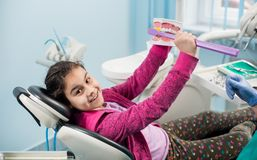 Smiling girl in dentist chair showing proper tooth-brushing using dental jaw model and big toothbrush in dental clinic. Dentistry, early prevention, oral royalty free stock images