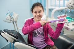Smiling girl in dentist chair showing proper tooth-brushing using dental jaw model and big toothbrush in dental clinic. Dentistry, early prevention, oral royalty free stock photography