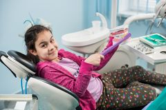 Smiling girl in dentist chair showing proper tooth-brushing using dental jaw model and big toothbrush in dental office. Dentistry, early prevention, oral royalty free stock image