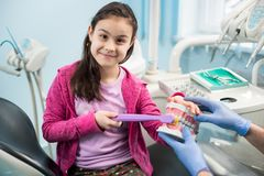 Girl in dentist chair showing proper tooth-brushing using dental jaw model and big toothbrush in dental office. Smiling girl in dentist chair showing proper royalty free stock photos