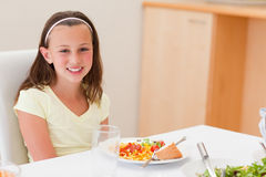 Smiling girl with dinner at the table Royalty Free Stock Image