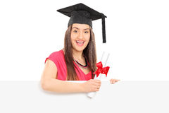 Smiling girl with diploma posing behind panel Stock Images