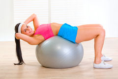 Smiling girl doing abdominal crunch on fit ball Royalty Free Stock Photos