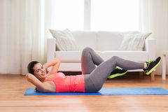 Smiling girl doing exercise on floor at home. Fitness, home and diet concept - smiling teenage girl doing exercise on floor at home royalty free stock images