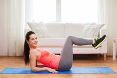 Smiling girl doing exercise on floor at home Stock Image
