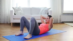 Smiling girl doing exercise on mat at home stock footage
