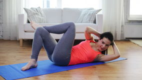 Smiling girl doing exercise on mat at home stock video footage