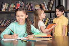 Smiling girl doing homework with classmates talking behind Royalty Free Stock Photography
