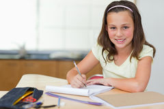Smiling girl doing homework in the kitchen Stock Image