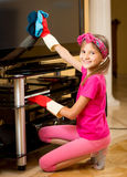 Smiling girl doing housework an cleaning big TV screen Royalty Free Stock Images