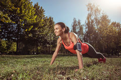 Smiling girl doing the plank on her outdoors training Royalty Free Stock Photos