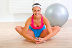 Smiling girl doing stretching exercises at home royalty free stock image