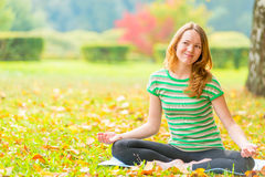 Smiling girl doing yoga in the park Royalty Free Stock Photos