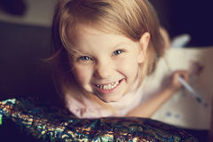 Smiling girl drawing Stock Images