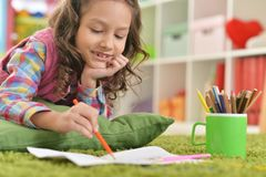 Smiling girl drawing at home royalty free stock image