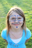 Smiling girl with drawings on face Royalty Free Stock Image