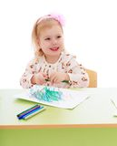 Smiling girl draws markers on a sheet of paper Royalty Free Stock Image
