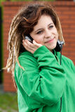 Smiling girl with dreadlocks listening to music Stock Photography
