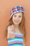 Smiling girl in dress raises thumbs-up Stock Image