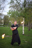 A smiling girl in dress shows a fire show. A smiling girl in a black dress shows a fire show Stock Photos