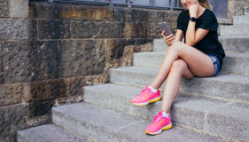 Smiling girl dressed in black T-shir, short denim shorts and pink sneakers sitting on stone steps and using smartphone Stock Photo