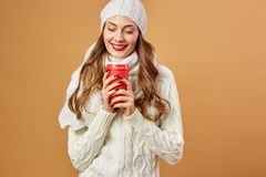 Smiling girl dressed in white knitted sweater and hat holds a red cup in her hands on a beige background in the studio.  stock photography