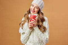 Smiling girl dressed in white knitted sweater and hat holds a red cup in her hands on a beige background in the studio.  royalty free stock image